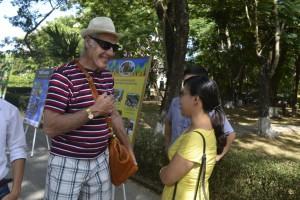 Khách du lịch thích thú dừng lại bên công viên để hỏi thông tin về liên hoan